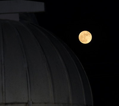 Supermoon rising over the observatory dome